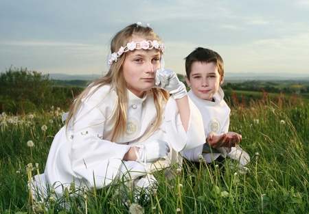 boy and girl in first holy communion on moody sky background, praying hands photo