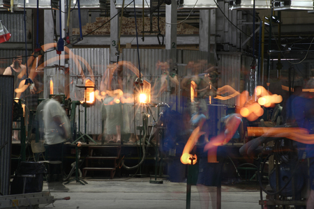 Glassblowers in movement creating glass articles Stock Photo