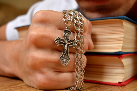 the believer: Orthodox cross in a strong hand