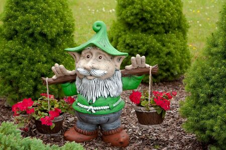 Elf holding red flowers in the garden Stock Photo