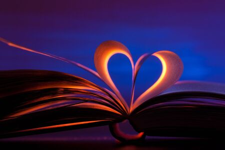 Open book in red heart shape on blue background Imagens