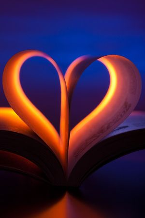 Open book in red heart shape on blue background photo