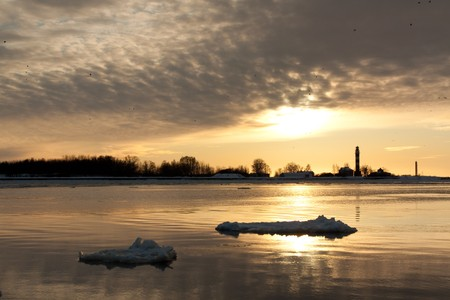 Lighthouse in sea on sunset in winter photo