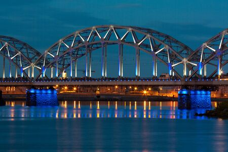 Night river with bridge and reflection in Riga photo