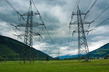 Wieże energii elektrycznej i cabels na tle chmur w Austrii