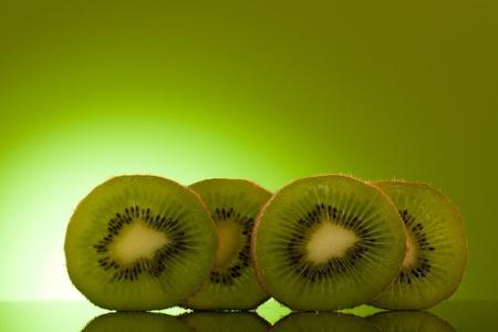 Green Kiwi in row on green background
