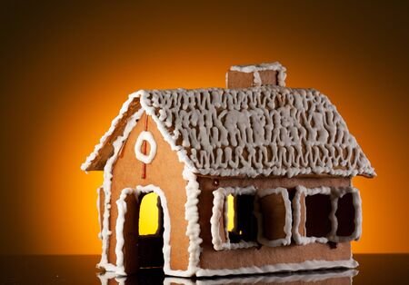 Gingerbread house on orange background photo
