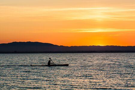 Man canoeing on sunset view photo