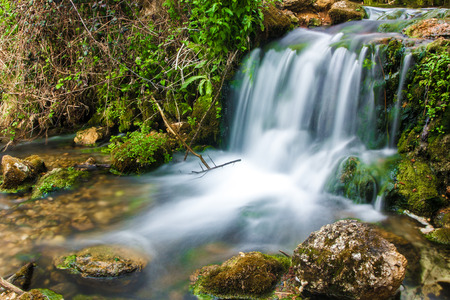 Waterfall with stones in wild nature