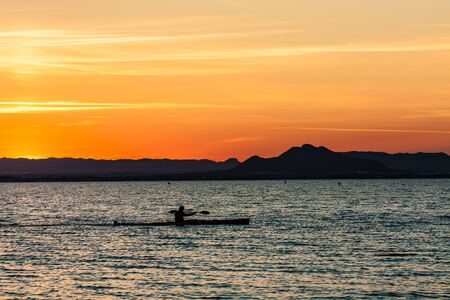 lake beach: Man canoeing on sunset view
