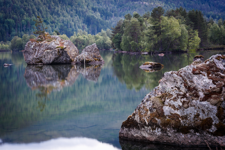 Stones in the lake with reflection in Norway Standard-Bild