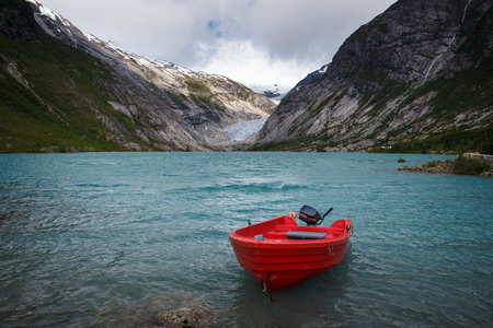 Nigardsbreen Glacier in Norway with lake and red boat