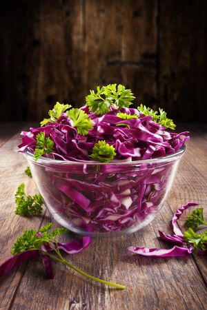 Red cabbage salad with green parsley with wood background Standard-Bild