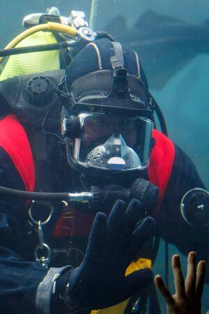 Diver saying goodbye to a kid in aquarium Standard-Bild