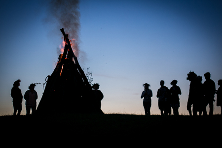 Bonfire with people silhouettes at night
