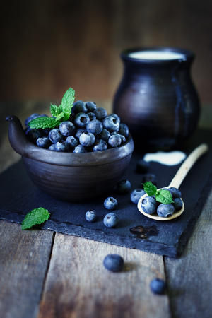 Blueberries with mint on a stone tray with milk Standard-Bild