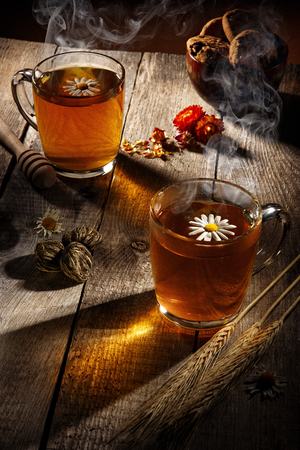 Cups with hot tea on a wooden table, rustic