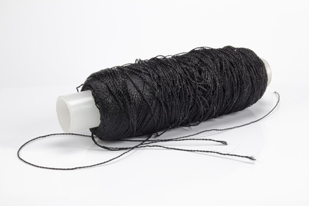 the rolled-up black sewing threads on a white background