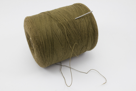 unwound: Ball of brown threads with a metal needle Stock Photo