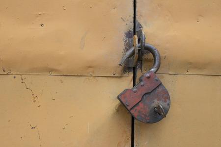 slovenly: The old hinged granary rusty lock on orange doors Stock Photo