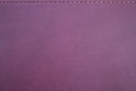 imitation leather: Texture of an imitation leather of crimson color with a seam
