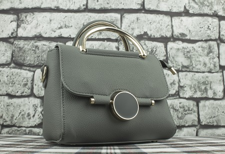 Modern fashionable bags against the background of gray bricks