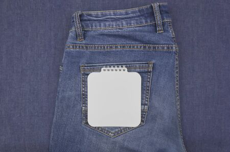 Classic blue jeans on a denim and notebook
