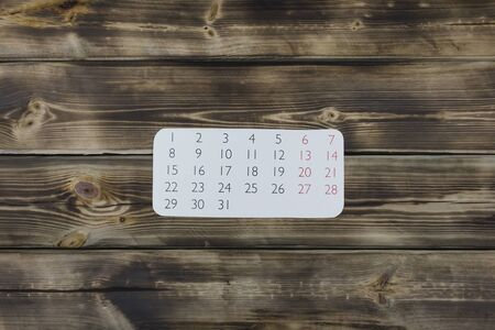 Sheet of a calendar month on a wooden natural background