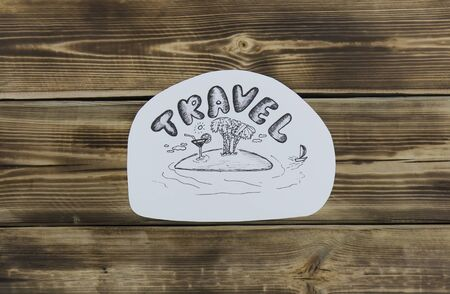 Paper sketch with island drawing on wooden background