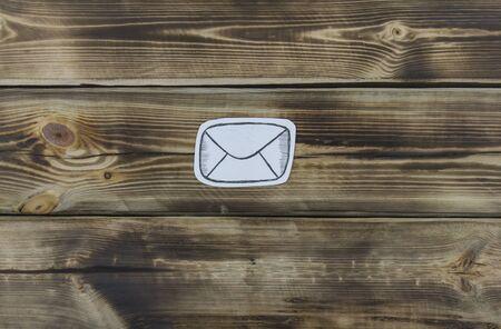 Paper sketch letter on natural wooden background