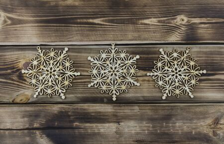 Wooden snowflakes on brown natural wood background