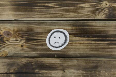 Boceto en papel de un rostro descontento sobre un fondo de madera