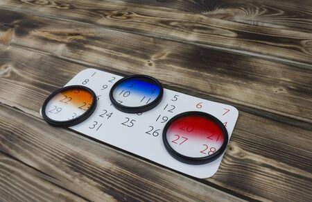 Calendar sheet and camera lens filter on wooden