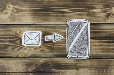 Paper drawn smartphone sketches and letters on wooden