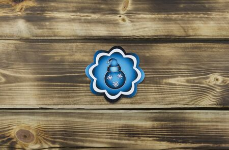 Blue sticker with Christmas illustration on wooden background