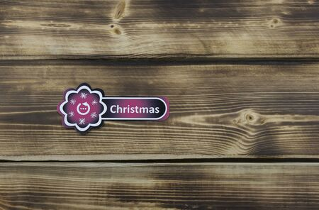 Red sticker with Christmas illustration on wooden background 스톡 콘텐츠