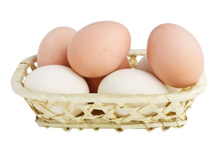 Chicken Eggs in A Woven Straw Basket isolated on white background photo