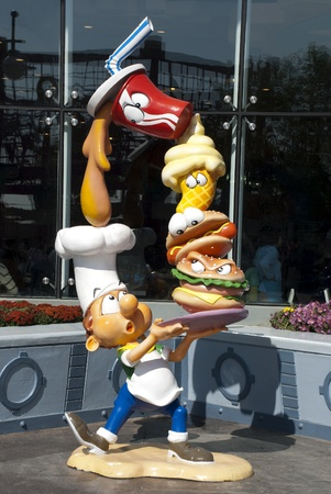 Discoveryland, Dalian, China - January 18, 2009: Funny sculpture of a new cook carrying foods & drink.