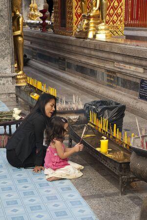 Chiang Mai, Thailand - 17. Januar 2006: Mutter lehrt ihre Tochter, wie man am Wat Suthep beten. Editorial