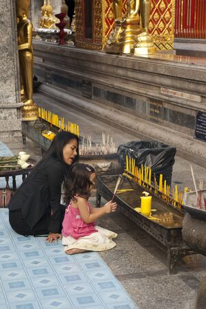 Chiang Mai, Thailand - January 17, 2006: Mother teaching her daughter how to pray at Wat Suthep.
