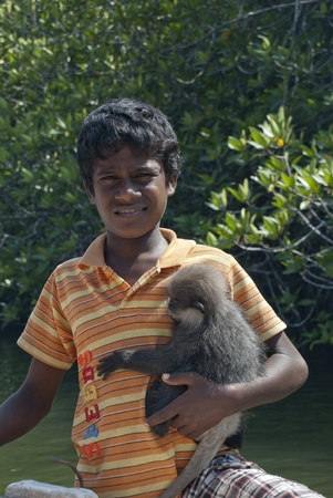 Hikkaduwa, Sri Lanka- March 03, 2012: Boy offering his monkey for photo.