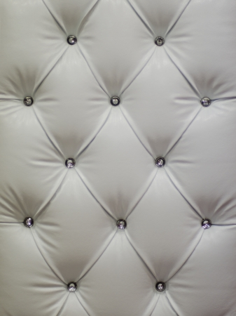 Photo of buttoned white upholstery leather as background.