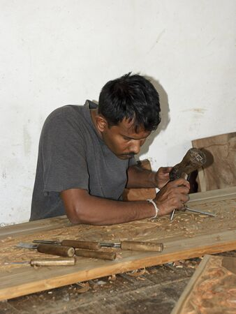 Kandy, Sri Lanka- March 06, 2012: Craftsman carving wood in Rajanima craft shop. Editorial