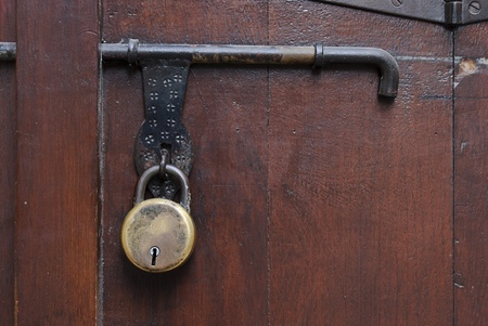 Old padlock, latch and padlock fittings on a wooden door. Stock Photo