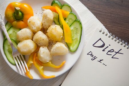 boiled potato on plate with cucumbers and paprika Stock Photo