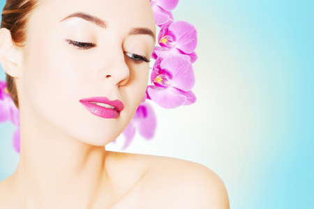 portrait of young european woman with clear skin and purple orchid flower in coiffure