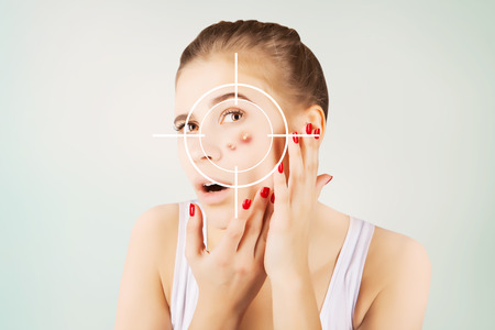 girl hunting for acne on her skin Stock Photo