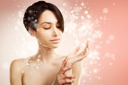 beautiful asian woman holds a product on snowy background Stock Photo