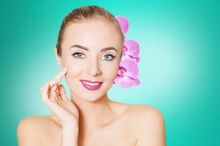 portrait of young caucasian woman with purple otchids, spa concept Stock Photo