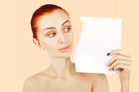 beautiful ginger haired woman watches blank paper